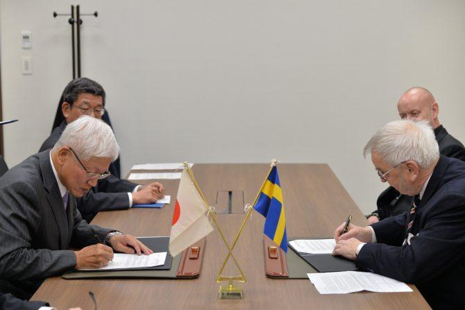 調印式で契約書に署名するホルムストロム氏(右)と松井社長
