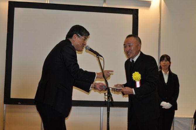 坂本区長(左)から記念プレートなどを受ける阿部常務